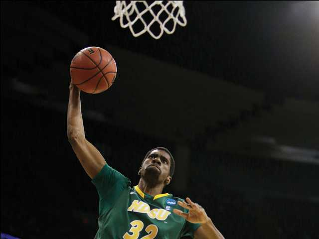 North Dakota State's TrayVonn Wright (32) goes up for a dunk against Oklahoma's Ryan Spangler (00) during the NCAA men's college basketball tournament in Spokane, Wash. on Thursday.