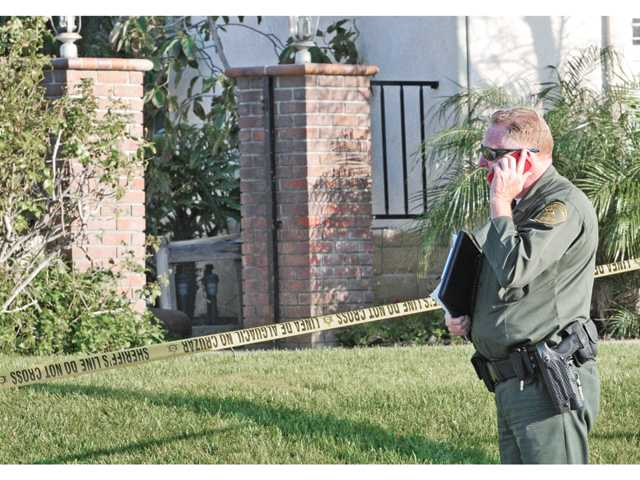 A Santa Clarita Valley sheriff's deputy stands in front of the home where a 4-year-old boy drowned Friday. Investigators say they don't know how the child got into the gated pool area. Signal photo by Dan Watson