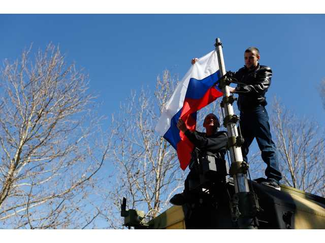 Two men hoist a Russian flag on a military vehicle after storming the base in Novofedorivka, some 50 km (30 miles) west of Simferopol, Crimea on Saturday.