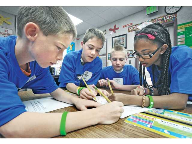 Sixth-grade team members, from left, Jonathan Kleinfeld, Michael Kleinfeld, Cameron Nale and Dania Salman, work out a perimeter and rate of speed math problem using algebra at the Math Field Day attended by 180 fourth-, fifth- and sixth-graders at Plum Canyon Elementary School in Saugus on Saturday.