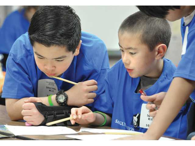 Sixth-graders Ethan Lewis, left, and Sage Kita and their team work out a perimeter and rate of speed problem using algebra.
