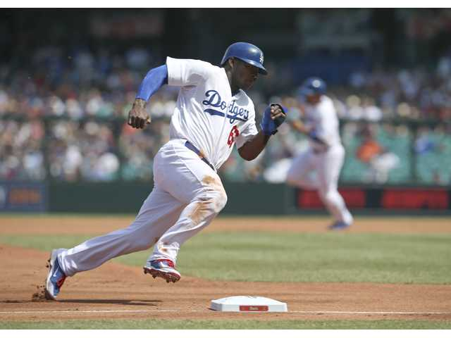 The Los Angeles Dodgers' Yasiel Puig rounds third on his way to scoring against the Arizona Diamondbacks in Sydney on Sunday.