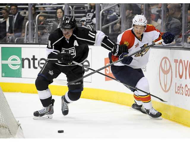 Los Angeles Kings' Anze Kopitar (11), and Florida Panthers' Nick Bjugstad (27) battle for the puck on Saturday in Los Angeles.
