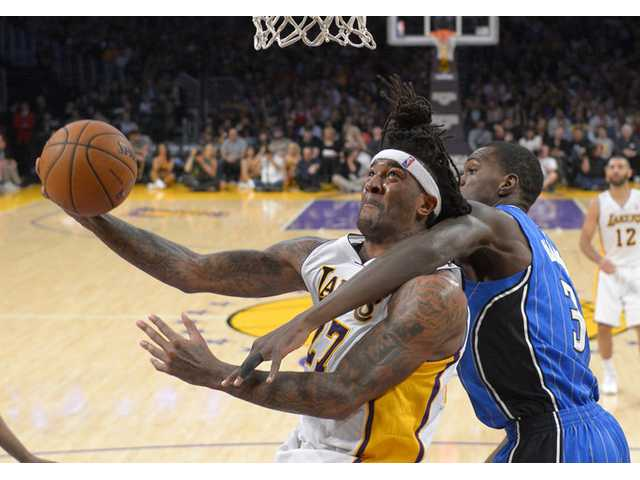 Los Angeles Lakers forward Jordan Hill, left, puts up a shot as Orlando Magic center Dewayne Dedmon defends on Sunday in Los Angeles.