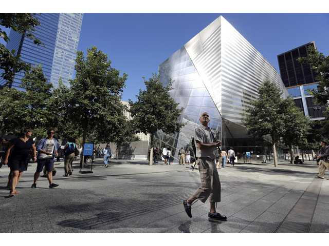 In this Sept. 6, 2013, file photo, a visitor to the National September 11 Memorial and Museum takes in the sight as he walks past the museum in New York.