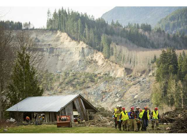 Rescue workers remove one of a number of bodies from the wreckage of homes destroyed by a mudslide near Oso, Wash. on Monday.