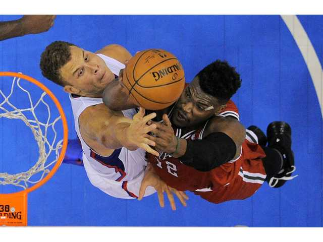 Milwaukee Bucks forward Jeff Adrien, right, goes up for a shot as Los Angeles Clippers forward Blake Griffin defends on Monday in Los Angeles.