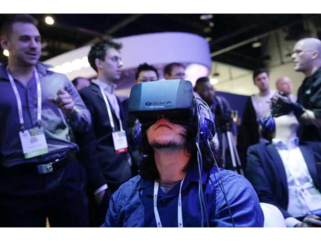 In this Jan. 7 photo, show attendees play a video game wearing Oculus Rift virtual reality headsets at the Intel booth at the International Consumer Electronics Show(CES), in Las Vegas.