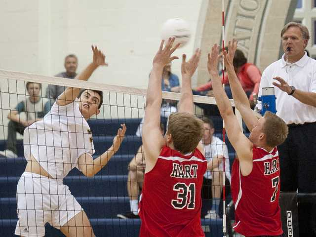 West Ranch outside hitter Andrew Dieterle, left, hits the ball into Hart blockers D.B. Gibbs (31) and Luke Maly (7) during Tuesday's Foothill League opening match at West Ranch High School.