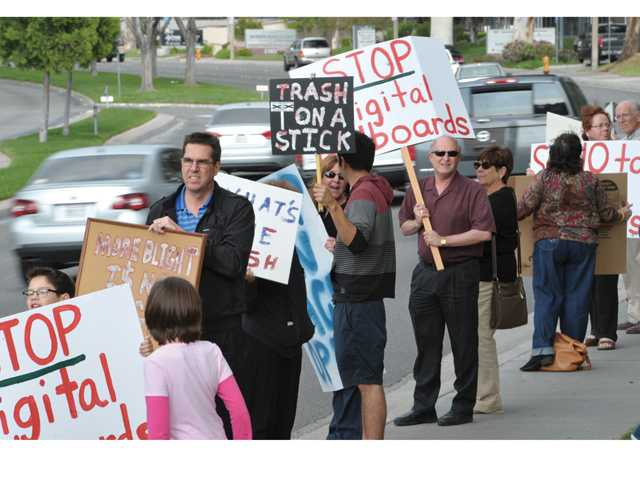 A group of citizens gather in front of Santa Clarita City Hall as they hold placards demonstrating against digital billboards in the Santa Clarita Valley on Tuesday evening. Signal photo by Dan Watson.
