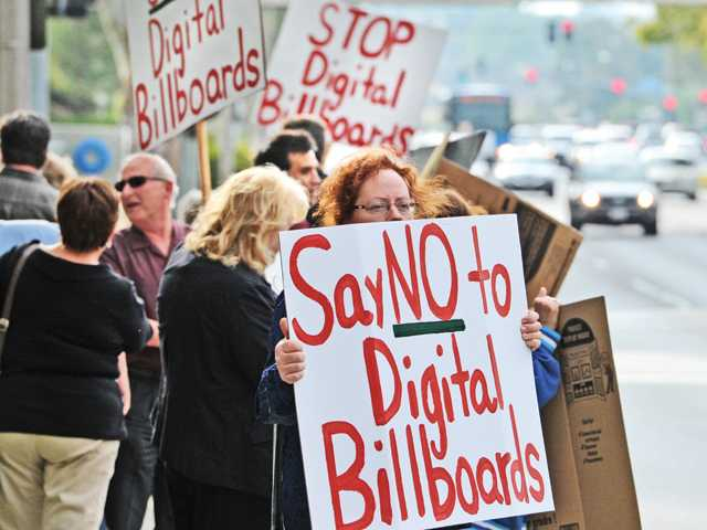 Sandra Balaram of Valencia stands with a group of about 35 citizens who gathered in front of City Hall as they hold placards demonstrating against digital billboards in Santa Clarita on Tuesday evening. Signal photo by Dan Watson.