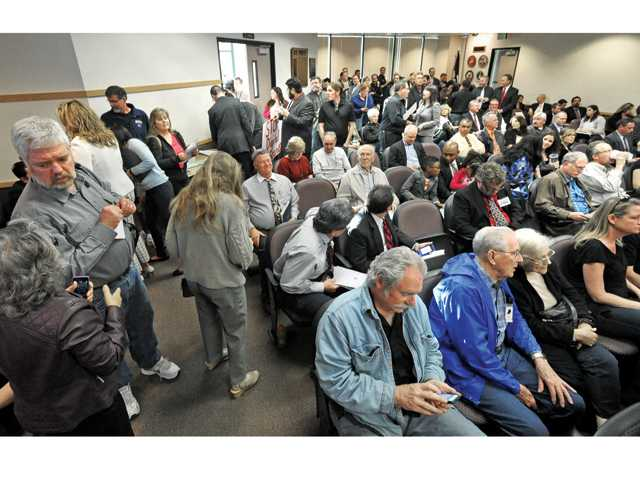 Members of the community crowd into the council chambers at Santa Clarita City Hall before the City Council meeting on Tuesday night, during which the council will give a final vote on the contentious billboard proposal with county Metro. Signal photo by Dan Watson.