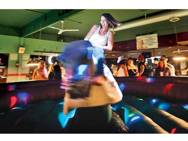 Katherine Gaussion tries to stay on the mechanical bull at Shooters Bar and Billiards and manages to last 49 seconds. Signal photo by Charlie Kaijo