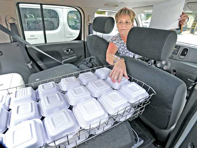 Santa Clarita Valley Senior Center home delivery volunteer Colleen Benn checks her list against the meals in the back of her van as she prepares to deliver Thanksgiving meals. While the Senior Center provides home-delivered meals on week days, the Thanksgiving feast meals are provided by the Castaic and Santa Clarita Valley Lions clubs.