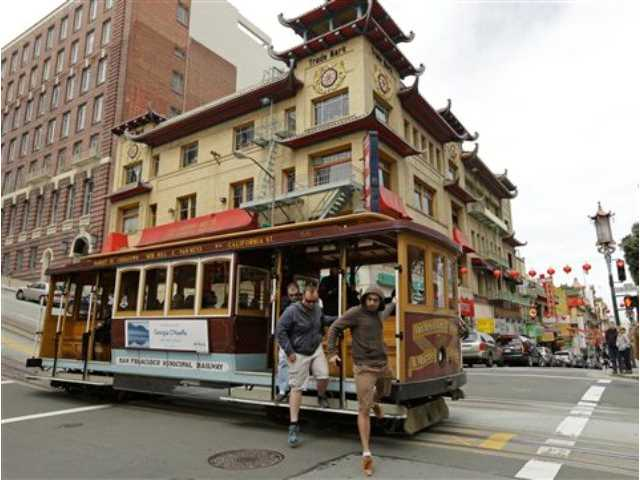 Passengers disembark a cable car in the Chinatown district Thursday, March 27, 2014, in San Francisco. Beneath the strings of red paper lanterns and narrow alleyways of the nation's oldest Chinatown lies an underworld, a place with a history of opium dens, gambling houses and gangland murders.