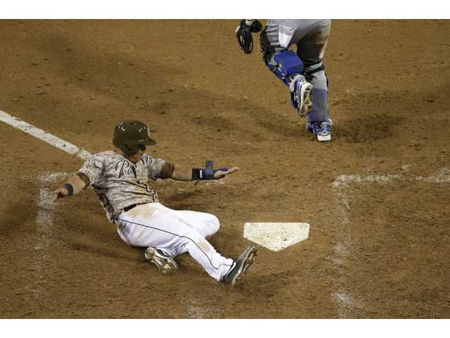 San Diego Padres' Everth Cabrera, left, slides in safely to home against the Los Angeles Dodgers on Sunday in San Diego.