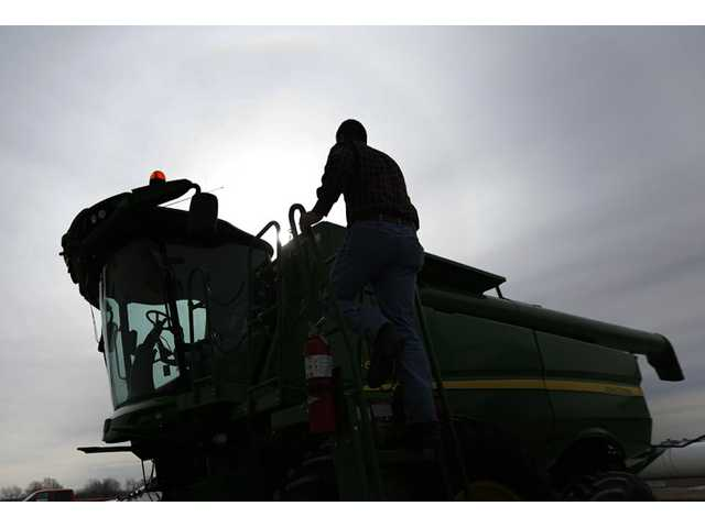 Nick Guetterman climbs into a combine on his farm near Bucyrus, Kan., on Feb. 19.