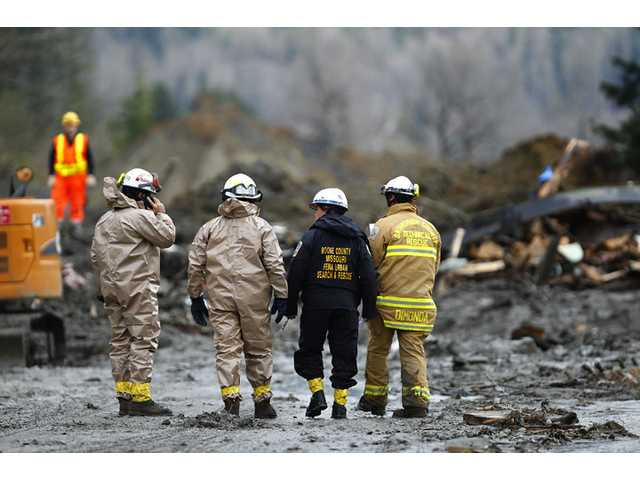 Rescue workers and work crews toil at the western edge of the mudslide where it covers Highway 530 Wednesday morning east of Oso, Wash.