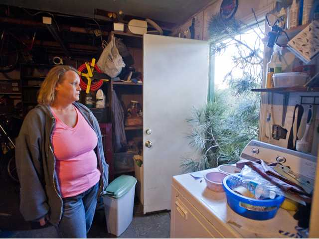 Brandi Hurst look at tree branches sticking into her garage from a pine tree that fell on her house Monday. Signal photo by Charlie Kaijo