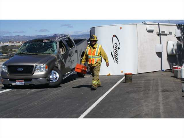 A paramedic with the Los Angeles County Fire Department packs up his gear on Interstate 5, near Valencia Boulevard, Sunday morning after the driver of a truck and over-turned trailer was taken to Henry Mayo Newhall Memorial Hospital with minor injuries. Signal photo by Jim Holt.