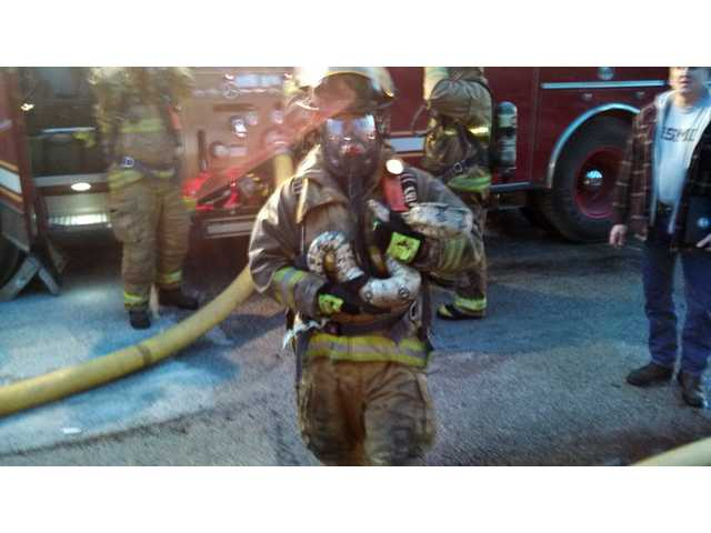 This photo provided by Gordon Cole, firefighter Scott Hemmelsbach holds a python after rescuing it from a burning home in Muskegon, Mich., on Sunday.