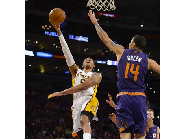 Los Angeles Lakers guard Kent Bazemore (6) drive on Phoenix Suns guard Gerald Green (14) on Sunday in Los Angeles.