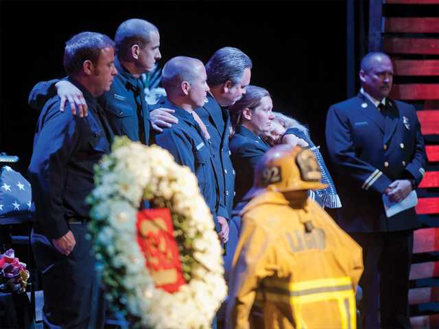 Crew members from Fire Station No. 92 stand on stage at the Real Life Church in Valencia on Monday to remember Paul Cooke, who died suddenly on March 18.