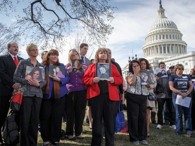 "Calling themselves ""GM Recall Survivors,"" families of victims of a GM safety defect in small cars hold photos of lost loved ones as they gather on the lawn on Capitol Hill."