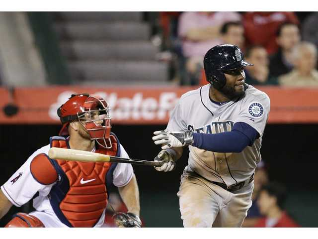 Seattle Mariners' Abraham Almonte, right, watches his RBI double against the Los Angeles Angels on Monday in Anaheim.