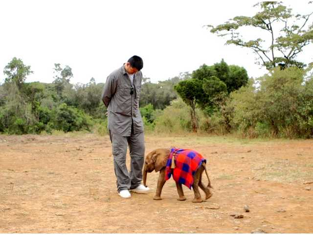 This undated image released by Animal Planet shows retired Chinese professional basketball player Yao Ming with a baby elephant.