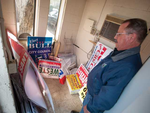 Community Preservation Officer Ron Brown looks at City Council election signs removed for violation of the city's sign ordinance. Signal photo by Charlie Kaijo