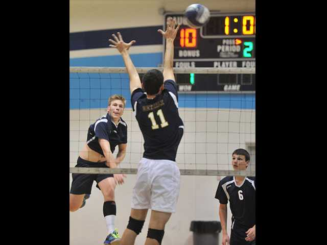 Saugus' Grant Spooner hits the ball as West Ranch's Andrew Dieterle goes up to block.