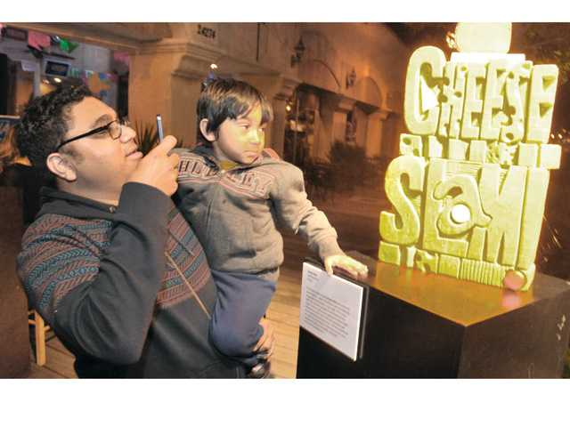 "Mittal Kapdi of Canyon Country takes a photo of his son Navaan, 5, with a sculpture of cheddar cheese carved by ""The Cheese Lady"" Sarah Kaufamn as it stands at the entrance to the Art Slam event held on Main Street in Newhall Thursday night. Signal photo by Dan Watson"