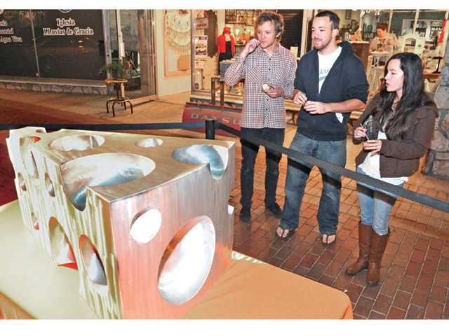 "From left, Devin Gonsalves, Jacob Boje, Gabrielle Gillette of Saugus view a 4-foot long aluminum sculpture entitled ""The Big Cheese"" on display at the Art Slam cheese themed event Thursday night in Newhall. Signal photo by Dan Watson"