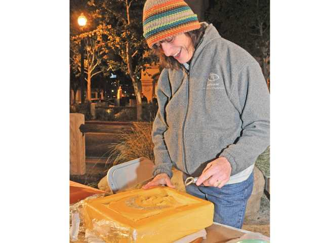 Local artist Lorelle Miller carves a face into a 20-pound block of cheese at Art Slam on Main Street in Newhall Thursday night. Signal photo by Dan Watson