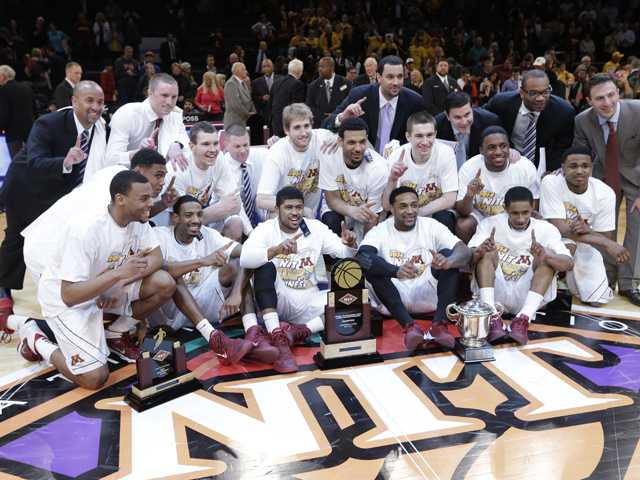 Minnesota coach Richard Pitino, right, and players pose for photos after the final of the NIT on Thursday in New York. Minnesota won the game 65-63.