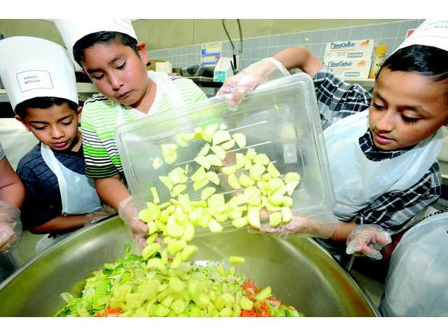 Canyon Springs Community School fourth-graders, from left, Daniel Medina, Jason Hernandez and Nathan Guzman pour vegetables into a bowl as they learn to make a salad during the 19th annual Kids' Cooking Campaign held at the Santa Clarita Valley School Food Services Agency in Valencia on Friday.