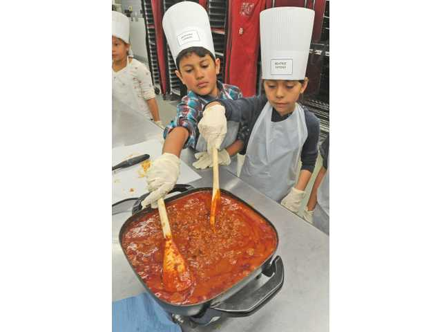 Anthony Landin, left, and Beatriz Patino stir the chili pot at the 19th annual Kids' Cooking Campaign held at the Santa Clarita Valley School Food Services Agency in Valencia on Friday.