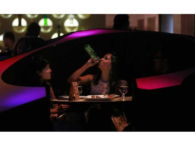 "In this April 2 photo, an Indian woman drinks with her friend at a night club ""blueFROG"" in Mumbai, India."