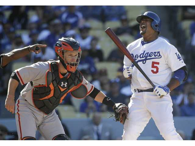 Los Angeles Dodgers' Juan Uribe, right, reacts while being tagged by Giants catcher Buster Posey after he struck out during the eighth inning in Friday's loss in Los Angeles.