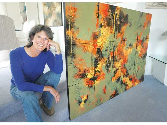 "Artist Nancy Eckels sits with her three-panel 54-by-72-inch acrylic painting called ""Fire and Sage"" at her home in Canyon Country."