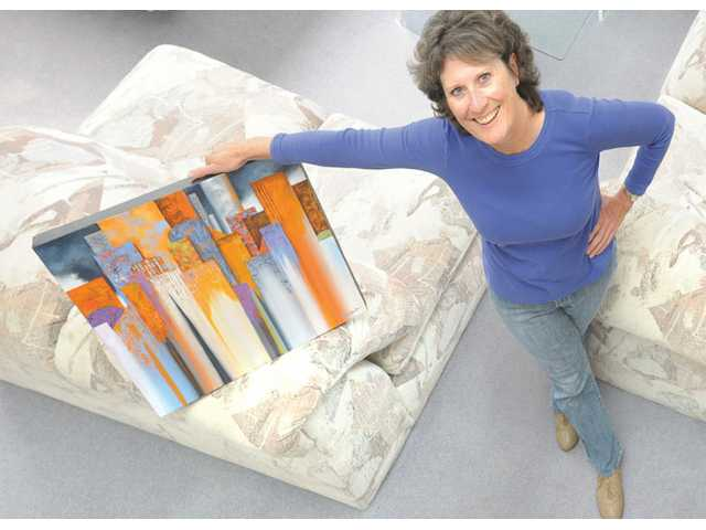 "Artist Nancy Eckels stands with her 20-by-20-inch acrylic paining ""Evening Skyline."""