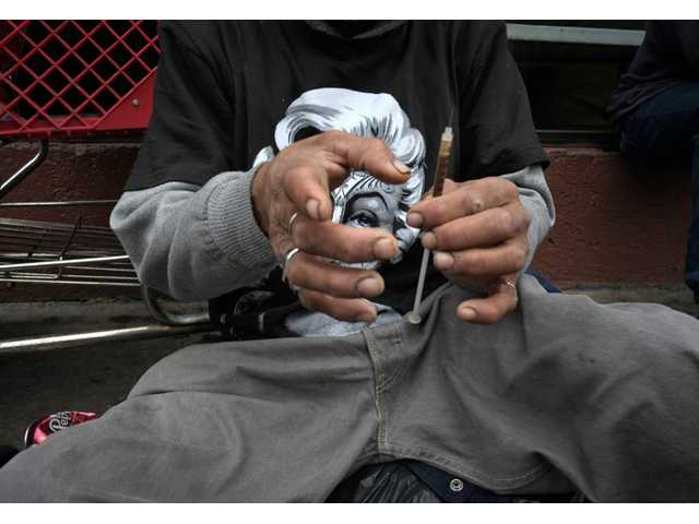 In this May 6, 2013 file photo, a drug addict prepares a needle to inject himself with heroin in front of a church in the Skid Row area of Los Angeles.