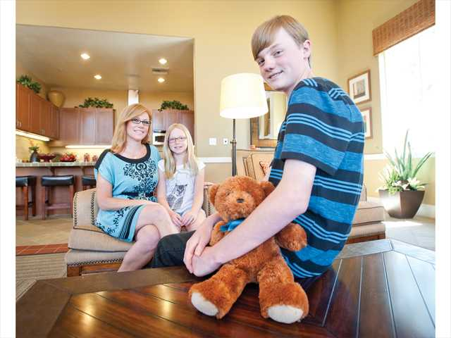 Miles Benson sits for a portrait with his mother, Amanda Benson, and sister, Audrey Benson, at the leasing office of their apartment in Valencia. Signal photo by Charlie Kaijo.