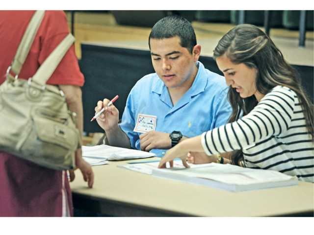 High school students Tito Gonzalez, 18, left, from Hart High and Tiffany Shroyer, 16, from Santa Clarita Christian School sign in voters at La Mesa Junior High School in Canyon Country on Tuesday. Signal photo by Dan Watson