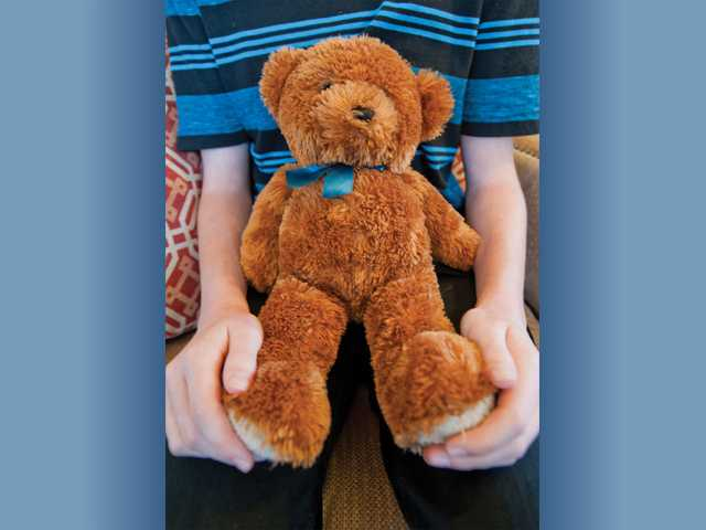 "Miles Benson holds his stuffed bear ""Stitchy,"" which a volunteer had given him when he was eight years old during an emergency room visit at Henry Mayo Newhall Memorial Hospital. Signal photo by Charlie Kaijo."