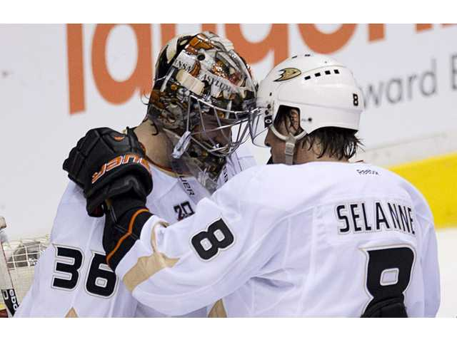 Anaheim Ducks Teemu Selanne (8) speaks with Anaheim Ducks goalie John Gibson (36) following their 3-0 win over the Vancouver Canucks in Vancouver on Monday.