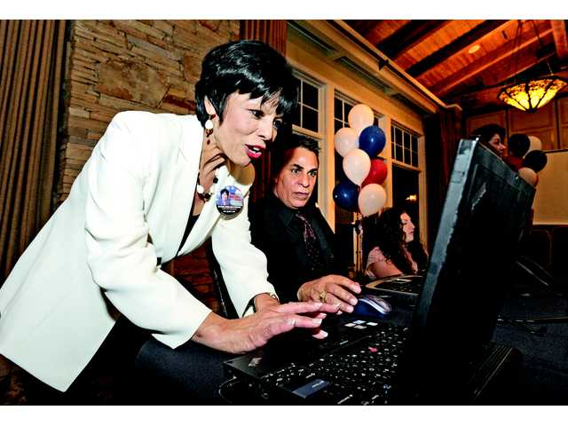 Gloria Mercado-Fortine sets up her computer to watch election returns at her election night party held at robinson Ranch Golf Club in Canyon Country. Signal photo by Dan Watson.