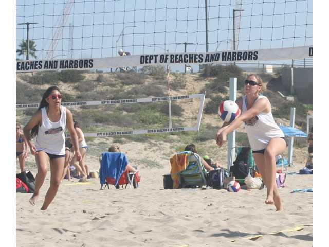 Trinity Classical Academy's Emily Buchanan, right, passes the ball as teammate Hannah Lee looks on during a beach volleyball competition at Dockweiler State Beach in Playa del Rey. Photo courtesy of Mike Buchanan.