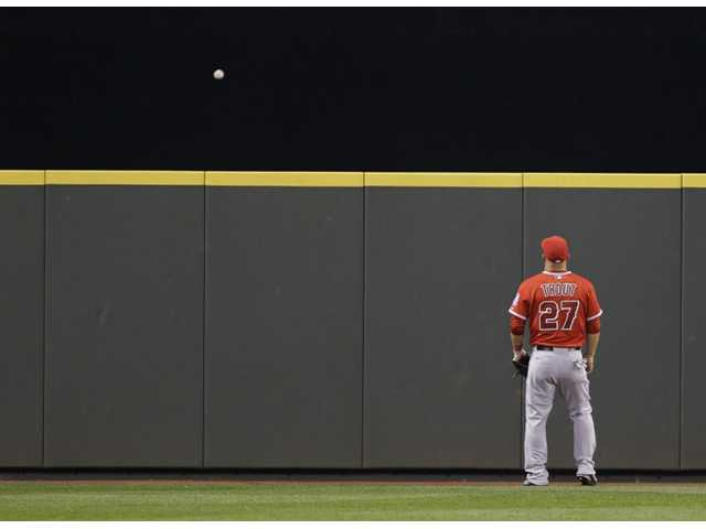 Los Angeles Angels center fielder Mike Trout can only watch as a solo home run hit by Seattle Mariners' Corey Hart goes over the wall in the seventh inning of Tuesday's game in Seattle.